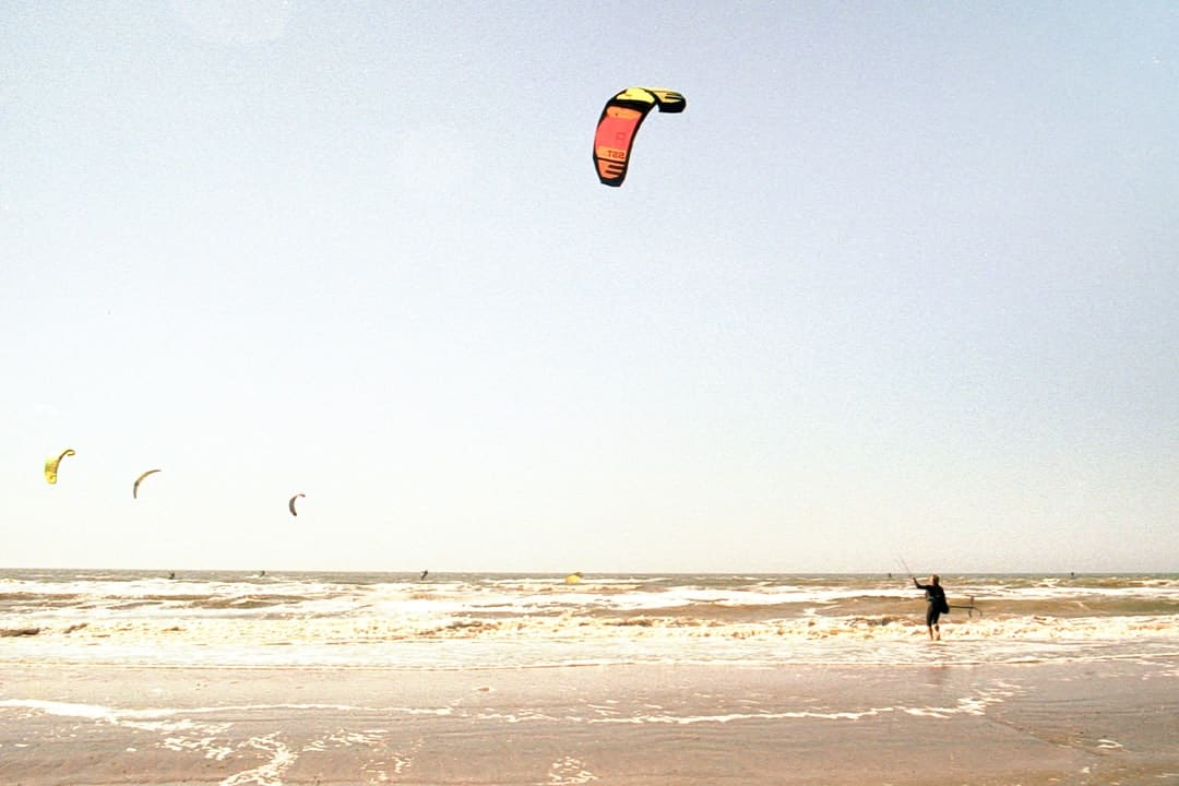 A group of people flying kites on a beach