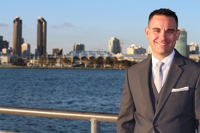 A man wearing a suit and tie standing next to a body of water